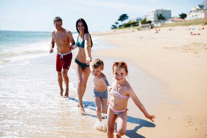 happy family in swimsuit having fun in the beach